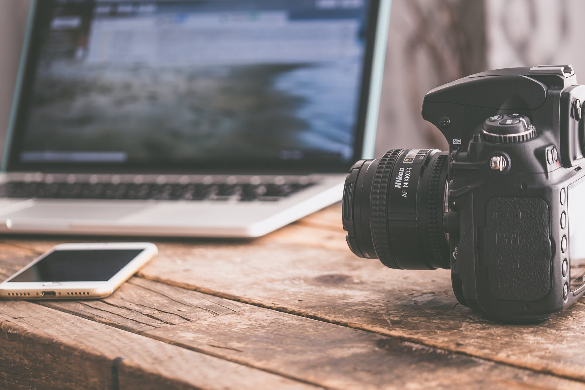 black dslr camera on beige wooden surface